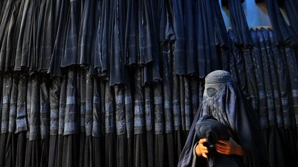 afghanische-frau-vor-einem-laden-fuer-burkas-die-geringste-abweichung-von-den-regeln-der-taliban-kann-frauen-das-leben-kosten-