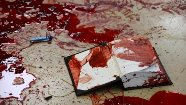 Handout photo of pools of blood seen near a religious Jewish text at the scene of an attack at a Jerusalem synagogue